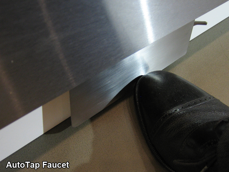 Man's foot touching the kick plate activated faucet for an automatic sink faucet