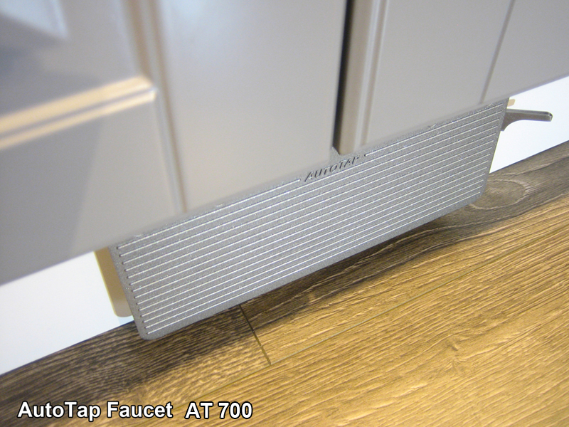 A hand free kick activated faucet is shown under cabinet door