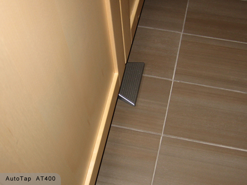 A touch faucet foot pedal valve is mounted under cabinet doors