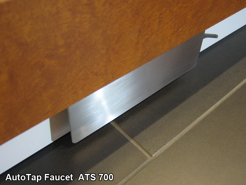 A stainless steel kick plate activated faucet is mounted under cabinet doors