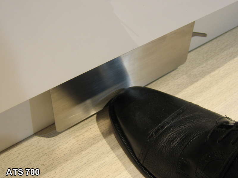 Man's foot touching a stainless kick activated faucet control